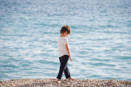 Photo for one lonely preschool kid in white jersey and blue trousers walking upset along sea beach in spring - Royalty Free Image