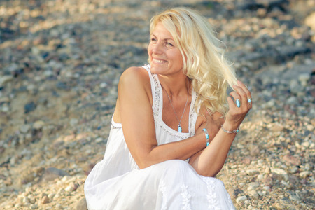 Foto für romantic portrait of a beautiful older woman. Mature beautiful blonde in a white dress walks on the  road - Lizenzfreies Bild