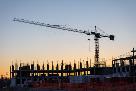 Photo pour Industrial construction cranes and buildings silhouettes at a construction site on the background at sunset or dawn. - image libre de droit