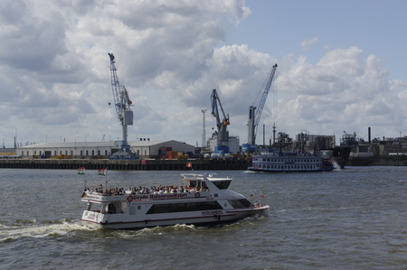 ferry in front of the Port of Hamburg with some container gantry cranes