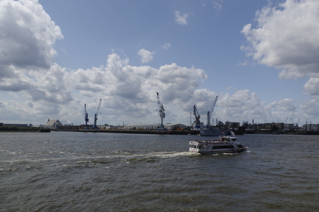 small ferry in front of the Port of Hamburg with some container gantry cranes
