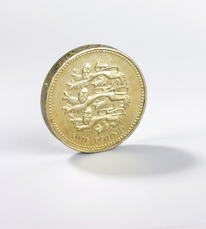 A british one pound coin standing on edge on a white background