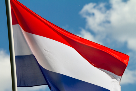 Flag of the Netherlands waving in the wind on flagpole against the sky with clouds on sunny day, close-up