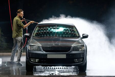 Photo pour Young man washing his car in car wash. Cleaning Car Using High Pressure Water. Washing with soap. - image libre de droit