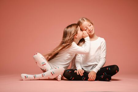 Photo pour Two cute little girls secrete with each other on a pink background in the studio. Kindergarten, childhood, fun, family concept. Two fashionable sisters posing. Gossip - image libre de droit