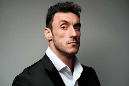 Photo pour Close up portrait of a man 30-34 years old in a white shirt and a black jacket on a gray background. A man with curly hair, big eyes and bristles shows different human emotions. - image libre de droit