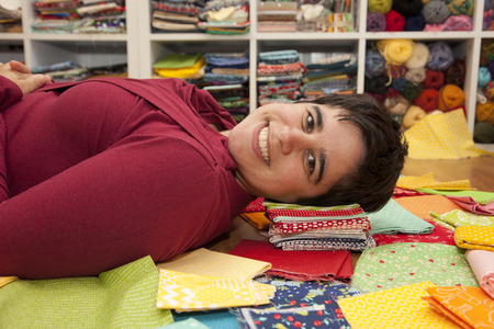 Happy craft person in their colorful craft space taking a break and smiling