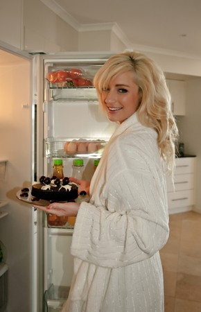 young woman getting food out of fridge for a late night snack