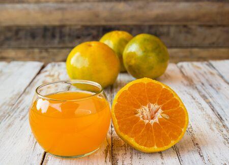 Glass of freshly pressed orange juice with sliced orange on wooden table background