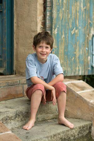 Photo pour Smiling boy sitting on steps - image libre de droit