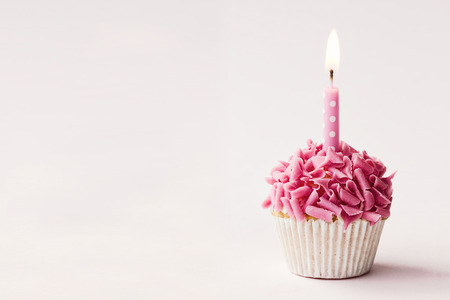 Foto de Cupcake decorated with pink chocolate curls and a single candle - Imagen libre de derechos
