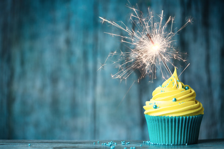 Photo for Cupcake with yellow buttercream and a sparkler - Royalty Free Image