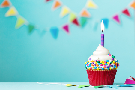 Photo for Colorful cupcake with single birthday candle - Royalty Free Image