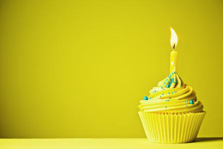 Foto de Cupcake decorated with a single yellow candle - Imagen libre de derechos