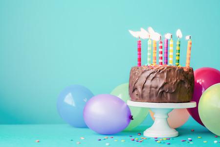 Foto de Chocolate birthday cake with colorful candles and balloons - Imagen libre de derechos