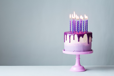 Foto de Birthday cake with drip icing and lots of purple candles against a gray background - Imagen libre de derechos