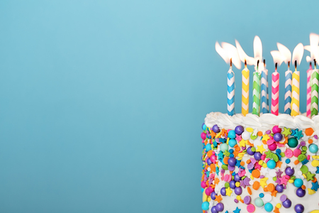 Birthday cake with lots of colorful candles and sprinkles on a blue background