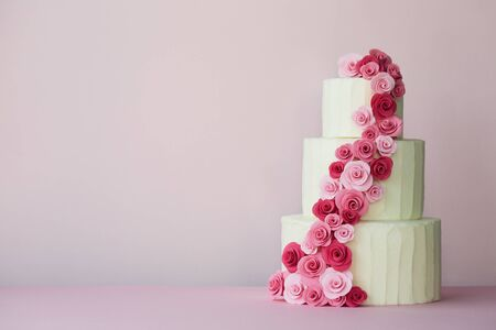 Photo for Tiered wedding cake with sugarpaste roses in pink - Royalty Free Image