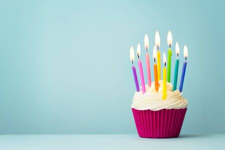 Photo pour Birthday cupcake with rainbow colored candles - image libre de droit
