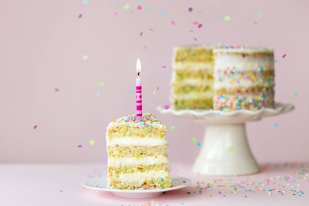 Photo pour Funfetti birthday layer cake with one candle and a single slice removed against a pink background - image libre de droit