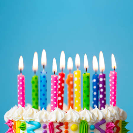 Photo pour Colorful birthday cake with rainbow colored candles - image libre de droit