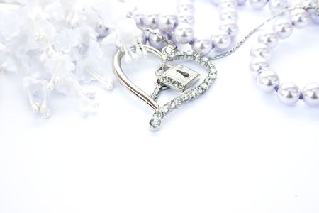 Photo pour Silver heart with key,lock,pearls and flowers on white background. - image libre de droit