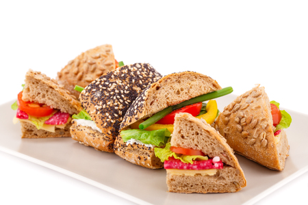 Sandwich with fresh vegetables, salami and cheese on plate.