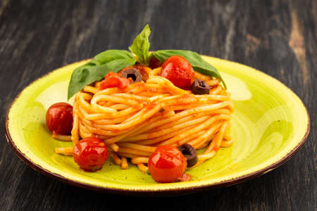 Photo pour Pasta spaghetti Napoli or Napolitana on green plate on black background. Italian cuisine. - image libre de droit