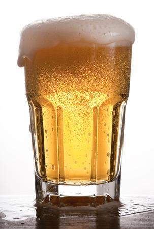 Glass of brimming beer. Studio shot. White background