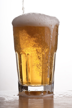 Glass of brimming beer. Studio shot. White background