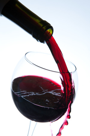 Red wine pouring into wine glass. Studio shot on white background.