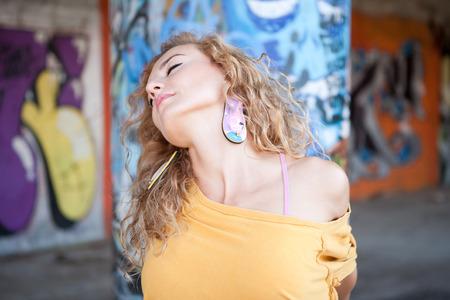 Teenage hip blond girl standing in front of graffiti wall. Outdoor portrait.