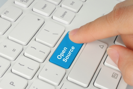 Hand pushing blue open source keyboard button