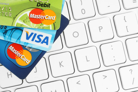 KIEV, UKRAINE - MARCH 21, 2015: Cards Visa and MasterCard are placed on white keyboard background. Online shopping, banking or paying concept.