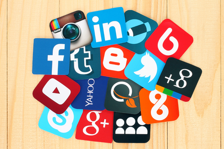 Photo pour Kiev, Ukraine - July 01, 2015: Famous social media icons such as: Facebook, Twitter, Blogger, Linkedin, Tumblr, Myspace and others, printed on paper and placed around on wooden background. - image libre de droit