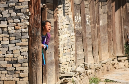 Woman of the Dong people at her home s door shouts loudly, apparently to nobody but seemingly in enmity with the whole village, repeatedly, entering the house and after a while getting out to shout again, time after time  Chongzhang, Guizhou, China