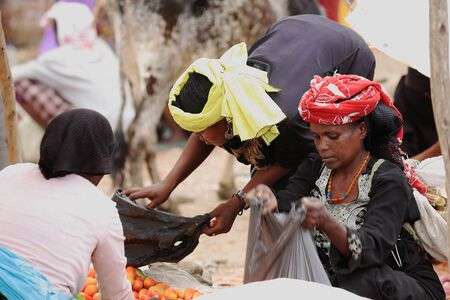 SENBETE, ETHIOPIA-MARCH 24: Local women do business in the sunday market where the oromo-amhara-afar peoples meet on March 24, 2013. Senbete-Oromia zone-Amhara region-Ethiopia.