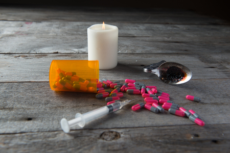 Drug paraphernalia including pills syringe, spoon, candle on a barn board background