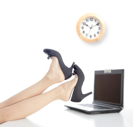 Relax Time in office, business woman take off high heels shoes with office background and a clock