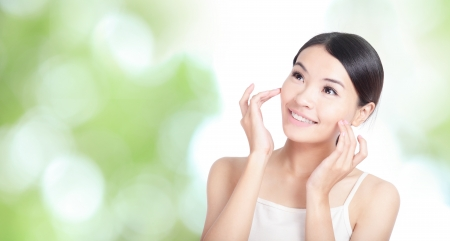 Young woman smile and hand touch face look to up forward concept for health body care with green nature background, model is a asian beautyの写真素材