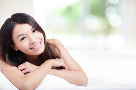 Photo pour Charming woman Smile face close up and she lying on the bed in the morning with nature green background, model is a asian girl - image libre de droit