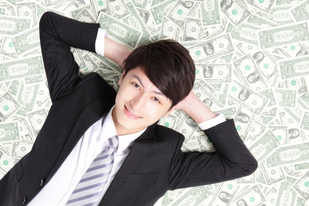 happy businessman lying on heap of dollars and smiling