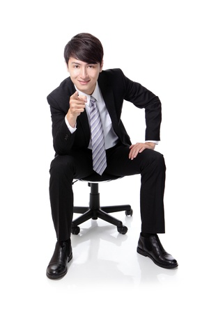 Smart businessman smiling and pointing to you while sitting in full length isolated on white background, asian model