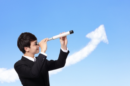 young business man against the blue sky looks through a telescope with growth arrow cloud. a symbol of leadership, success and freedom.