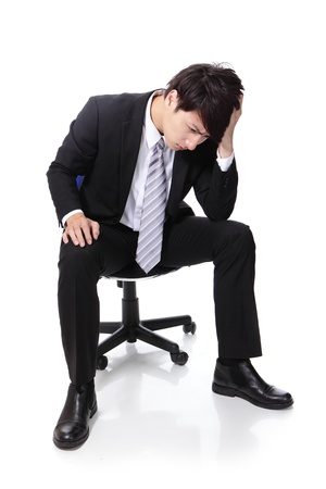 Frustrated and thinking business man is sitting on chair, full length, isolated on white background
