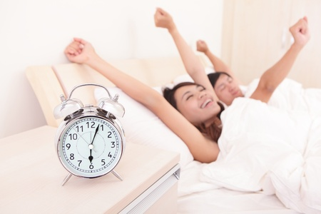 happy Couple wake up in Bed and smiling raise arms in the morning, asian lovers