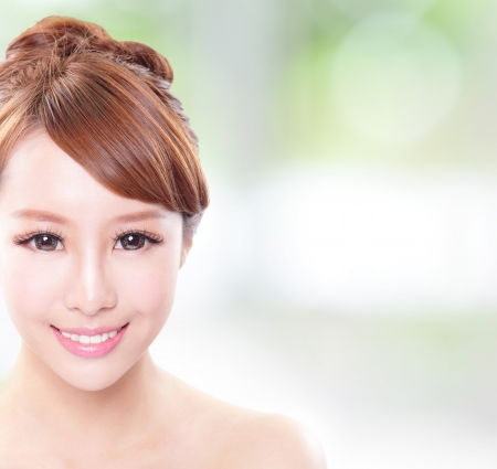 portrait of the woman with beauty face and perfect skin and health teeth isolated on green background, with copy space in the image, asian model