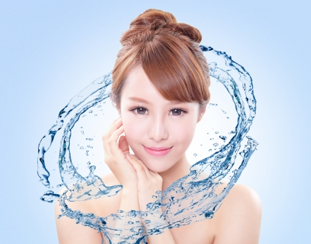 Photo pour Beautiful portrait of woman with fresh skin in splashes of water , concept for beauty skin care isolated on blue background, asian model - image libre de droit