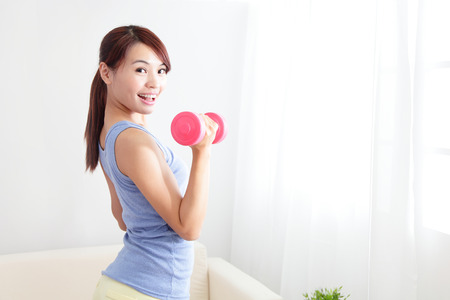 beautiful sporty woman working out with two dumbbells , asian beauty model