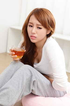 Portrait of woman with stomach ache sitting on floor at home, asian model